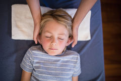 Overhead view of boy with eyes closed receiving neck massage from female therapist stock images