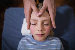 Overhead view of boy receiving head massage from female therapist stock image