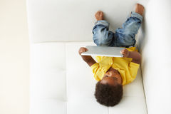 Overhead View Of Boy On Sofa Playing With Digital Tablet Royalty Free Stock Photography