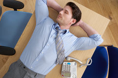 Overhead View Of Businessman Lying On Desk In Office Stock Images