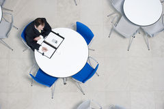 Overhead view of businessman at table of staff canteen, looking through business papers Stock Images