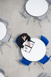 Overhead view of businessman at table of staff canteen, looking through business papers stock photos