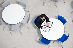 Overhead view of businessman at table of staff canteen, looking through business papers Stock Photography