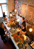 Overhead view of cafe counter marmelade. Looking down onto a food counter in a cafe with cakes and salads on it, there are two people working behind the counter Stock Images