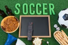 Chalkboard, snacks and football on artificial grass. Overhead view of chalkboard, snacks and football on artificial grass stock image