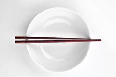 Overhead view of chopsticks lying across an empty bowl Stock Images
