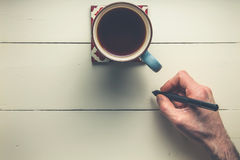 Overhead view of cofee and hand with pen on wood Royalty Free Stock Photo