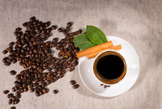 Overhead view of coffee bean pile by mug on canvas Royalty Free Stock Image