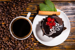Overhead view of coffee beans beside dessert. Overhead view of coffee beans beside white mug and dessert decorated with chocolate and red berries on a wood table Royalty Free Stock Photos