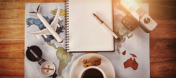 Overhead view of coffee cup with camera and diary map. At table Royalty Free Stock Image
