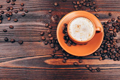 Overhead view of coffee cup. Overhead view of Ceramic orange cup of coffee with foam and coffee beans, standing on wooden table Stock Photography