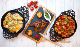 Overhead view of colorful roast vegetables, savory sauces served Stock Image