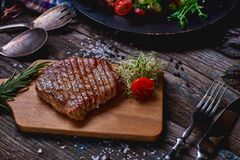 Overhead view of colorful vegetables, savory sauces and salt served with grilled steak on a rustic wooden counter in a country ste. Akhouse with a copy space Stock Photography