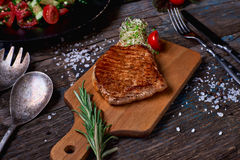 Overhead view of colorful vegetables, savory sauces and salt served with grilled steak on a rustic wooden counter in a country ste. Akhouse with a copy space Royalty Free Stock Image