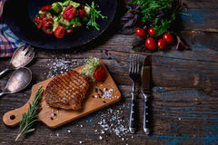 Overhead view of colorful vegetables, savory sauces and salt served with grilled steak on a rustic wooden counter in a country ste. Akhouse with a copy space Royalty Free Stock Photos