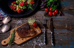 Overhead view of colorful vegetables, savory sauces and salt served with grilled steak on a rustic wooden counter in a country ste. Akhouse with a copy space Stock Photo