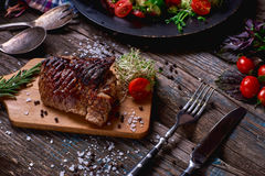 Overhead view of colorful vegetables, savory sauces and salt served with grilled steak on a rustic wooden counter in a country ste. Akhouse with a copy space Royalty Free Stock Images