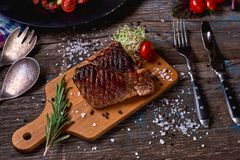 Overhead view of colorful vegetables, savory sauces and salt served with grilled steak on a rustic wooden counter in a country ste. Akhouse with a copy space Stock Photos