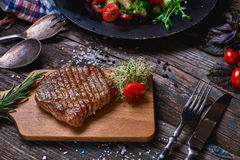 Overhead view of colorful vegetables, savory sauces and salt served with grilled steak on a rustic wooden counter in a country ste. Akhouse with a copy space Stock Images