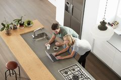 Overhead View Of Couple Looking At Laptop In Modern Kitchen Royalty Free Stock Image