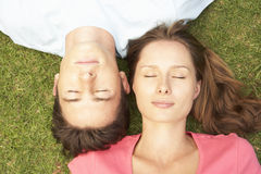 Overhead View Of Couple Lying On Grass With Eyes Closed Stock Photo
