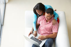 Overhead View Of Couple Relaxing On Sofa Using Laptop Royalty Free Stock Photos