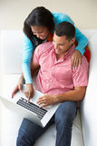 Overhead View Of Couple Relaxing On Sofa Using Laptop Royalty Free Stock Image