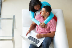 Overhead View Of Couple Relaxing On Sofa Using Laptop Stock Photos