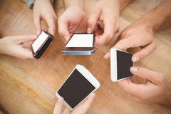 Overhead view of cropped hands using smartphones Stock Photography