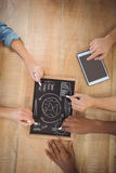 Overhead view of cropped hands writing business terms on slate with person using digital tablet Royalty Free Stock Images