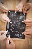 Overhead view of cropped hands writing business terms on slate Royalty Free Stock Image