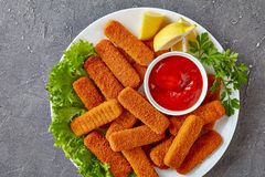 Overhead view of crumbed fish sticks stock images