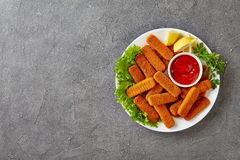 Overhead view of crumbed fish sticks stock photography