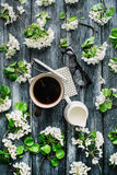 Overhead view of cup of black coffee, milk, pen, glasses and white flowers and branches  on white background Stock Photos