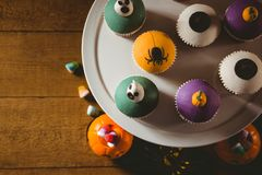 Overhead view of cup cakes with decorations on table during Halloween Stock Images
