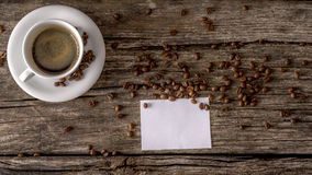 Overhead view of cup of freshely prepared black coffee and blank Royalty Free Stock Photo