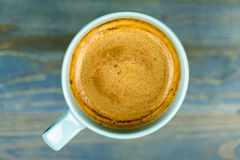 Overhead view of a cup of frothy coffee. Overhead view of a cup of frothy cappuccino coffee on a blue painted weathered wooden table Stock Images