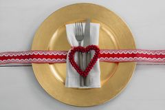 Cutlery with napkin and christmas decoration in a plate. Overhead view of cutlery with napkin and christmas decoration in a plate Royalty Free Stock Image