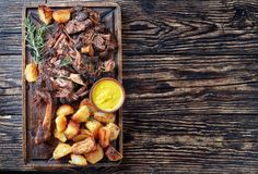 Overhead view of delicious slow roast tender leg of lamb pulled off the bones and served with crispy roast potatoes on a wooden. Tray on a rustic wooden table stock image