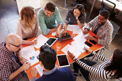Overhead View Of Designers Having Meeting Around Table Royalty Free Stock Images