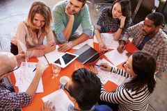 Overhead View Of Designers Having Meeting Around Table Stock Photos