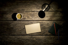 Overhead view of desk lamp, coffee, notebook and blank piece of Stock Photo