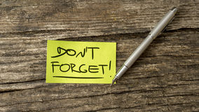 Overhead view of a Don't forget reminder message. Written on green piece of paper lying on a textured wooden desk next to a silver pen Royalty Free Stock Photos