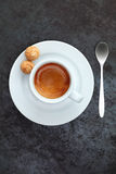 Overhead view of espresso coffee in a cup. Overhead view of strong frothy espresso coffee in a cup and saucer with two traditional macaroons and a silver Royalty Free Stock Photo