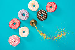 Overhead view of food composition with several donuts with various glaze on blue Royalty Free Stock Photos