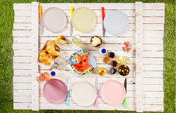 Overhead view of food on a summer picnic table. Overhead view of food and empty plates on a summer picnic table outdoors on the grass with croissants, watermelon Stock Image