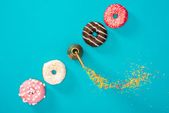 Overhead view of four donuts with colorful glaze in row. Donuts royalty free stock image