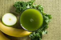 Fresh kale juice in glass with fruits on place mat Royalty Free Stock Photography