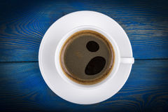 Overhead view of a freshly brewed mug of espresso coffee on blue rustic wooden background with woodgrain texture. Coffee break Stock Photography