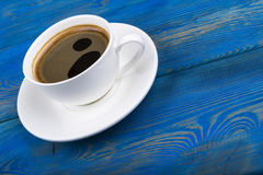 Overhead view of a freshly brewed mug of espresso coffee on blue rustic wooden background with woodgrain texture. Coffee break Stock Image